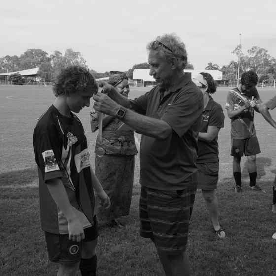 Charlie presenting the NO MORE Campaign Sportsmanship Medal to Palmerston player Cory.