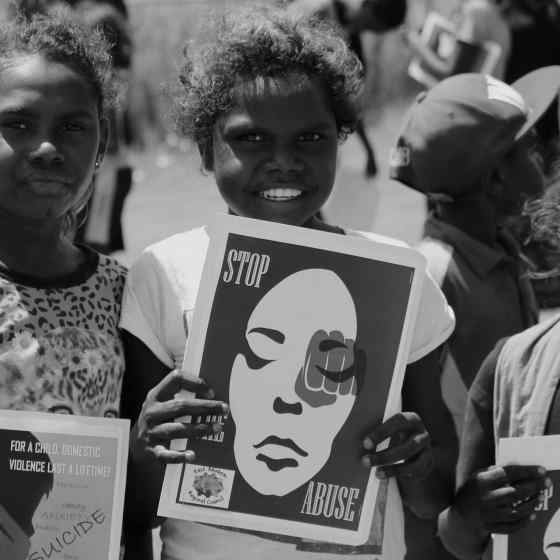 Children hold signs standing up against family violence.