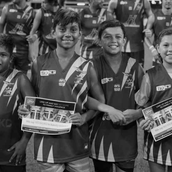 Wanderers FC juniors link arms before the match.