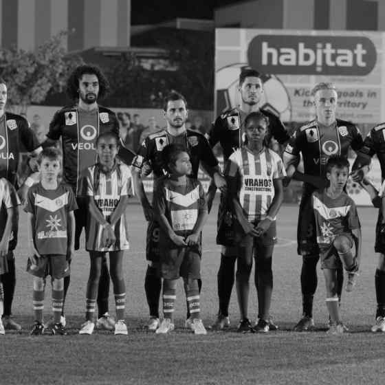 Adelaide United FC stand united with junior players from Darwin Olympic SC before the FFA Cup Round of 32 match in Darwin.