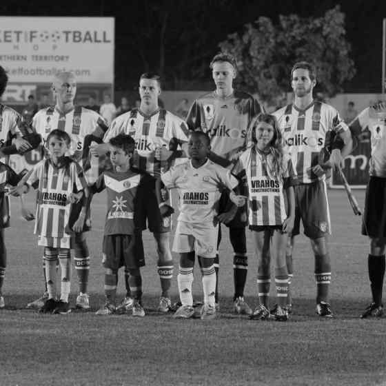 Darwin Olympic SC players link up before the match played in front of 2,300 local and interstate supporters.