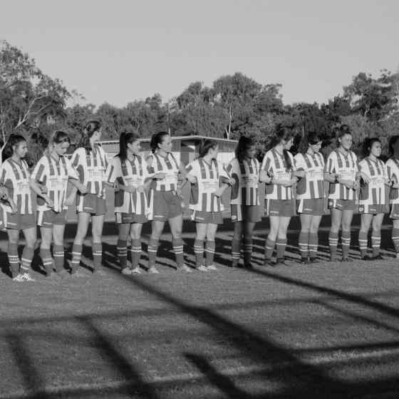 Darwin Olympic women's team link arms before the match.