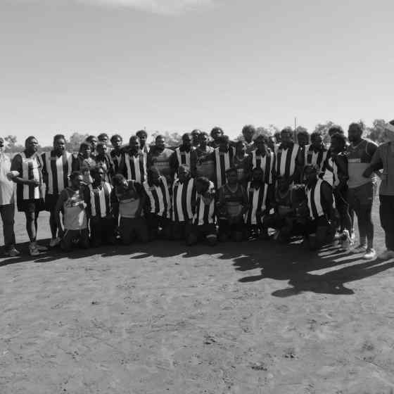 Mulga Bore links arms with Laramba Cowboys after winning the Div. 2 competition.